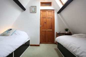 Lodge second bedroom with two single beds and vaulted ceiling